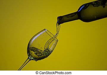 Whine Pouring Out of Bottle On The Right Hand Side to Wineglass with Colorful Liquid and Droplets.