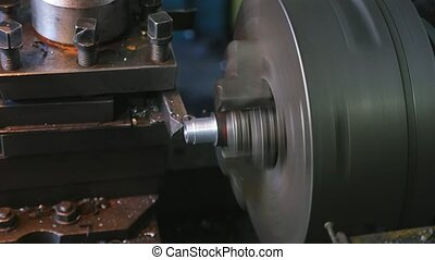 Whirling cylinder on a lathe machine peeling metallic chips...
