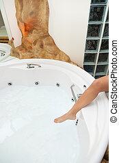 Whirlpool bath - White whirlpool bath with rock ready to...