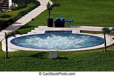 Whirlpool in Resort Grass - A round bubbling whirlpool in...