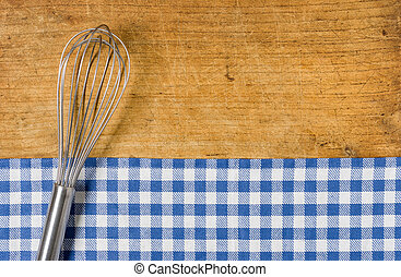 Whisk on wooden background with a blue checkered tablecloth