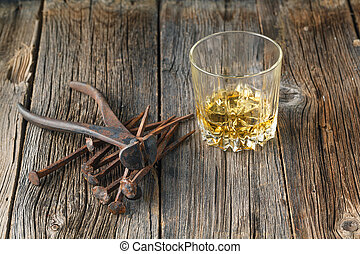 Whiskey and rust tools on wooden table