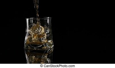 Whiskey being poured into a glass against black background. Long shot. Slow motion.