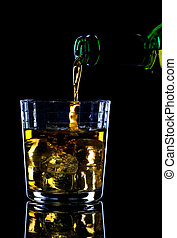 Whiskey being poured into a glass of ice against a black background.