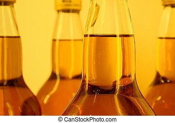 Whiskey Bottles - Full whiskey bottles on an amber...