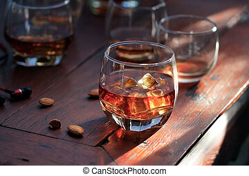 Whiskey bourbon in a glass with ice on wooden table background