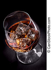 Whiskey / Cognac on black background - photo of whiskey...