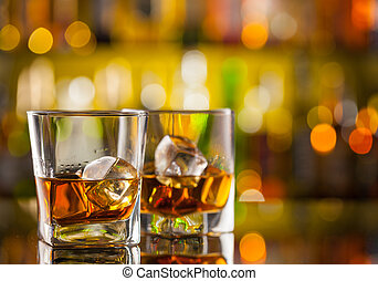 Whiskey drinks on bar counter with blur botles on backgorund