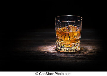 Whiskey - Glass of whiskey on wooden background close up