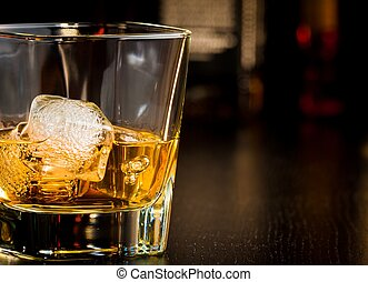 whiskey glass with ice in front of bottles with space for text