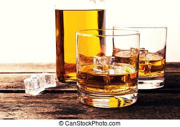 whiskey glasses and bottle on wooden table against white background