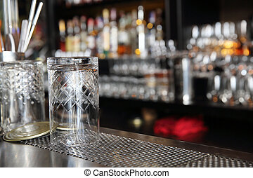 Whiskey glasses on bar counter with blur bottles background