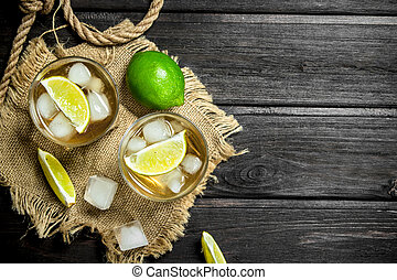 Whiskey in a glass with lime and ice on the sack.