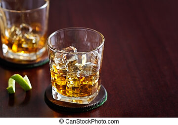 whiskey in glass on wooden background, blank text