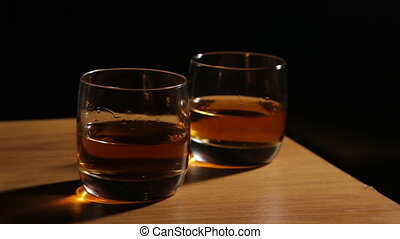 Whiskey in glasses - Glasses of whiskey with ice on wooden...