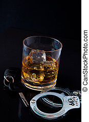 Whiskey on the rocks with car key and handcuff against a...