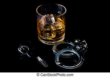 Whiskey on the rocks with handcuff and car key against a...