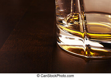 Whiskey - Part of the whiskey glass over a dark wooden table