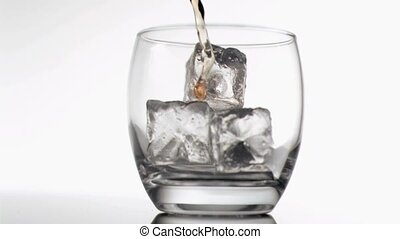 Whiskey poured in super slow motion in a glass with ice