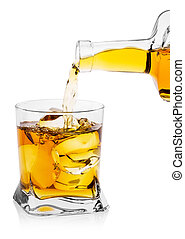 Whiskey pouring from bottle into transparent glass with ice