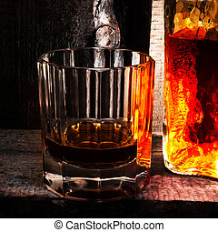 Whiskey Scotch glass and a bottle on old wooden background. ...