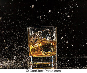 Whiskey splashing around glass, isolated on black background