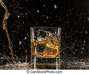 Whiskey splashing around glass, isolated on black background