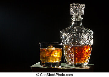 Whiskey with glass and carafe on book