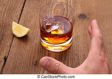 Whiskey with ice cubes in glass and grab hand, close up