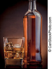 whiskey with ice cubes in glass near bottle on black background, warm atmosphere