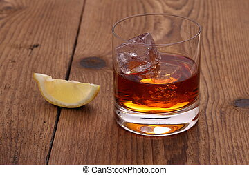 Whiskey with ice cubes in glass on wood