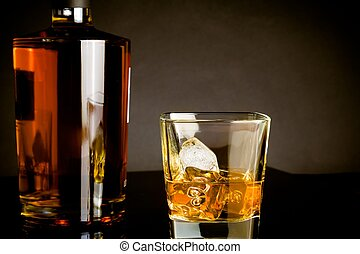 whiskey with ice in glass near bottle on dark background