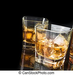 whiskey with ice in glasses near bottle on black background