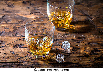 Whiskey with ice in glasses on rustic wood background, copy ...