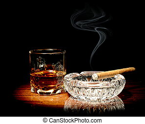 Whisky and a cigar - Studio shot of whisky in a glass and a...