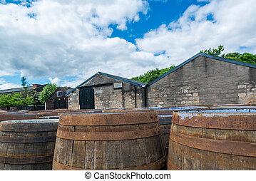 Whisky barrels at a Scottish distillery - Whisky barrels in...