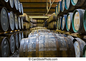 Whisky barrels in a distillery - Whisky barrels maturing in...