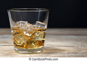 Whisky in glass with ice cubes on wooden board