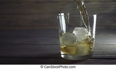 Whisky is poured into glass in slow motion