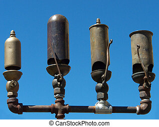 Four antique brass steam engine train whistles, ready to blow