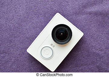 White action camera with a large black lens on a violet background