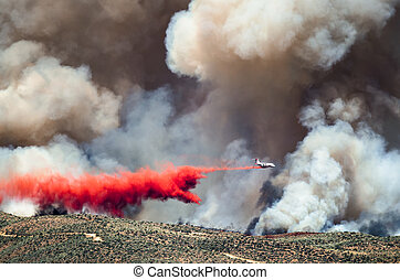 White Aircraft Dropping Fire Retardant as it Battles the ...