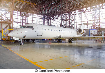 White aircraft in the hangar on a large-scale inspection, repair.