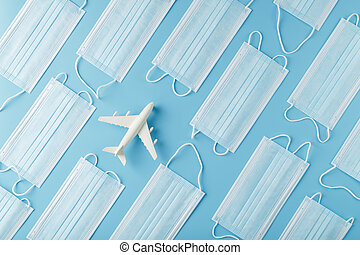 White airplane around protective masks on a blue background