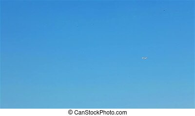 White airplane flying in blue sky