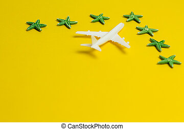 white airplane model and green starfishes in the corner of yellow background