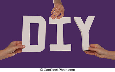 White alphabet lettering spelling DIY held up over a purple...