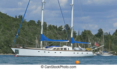 White Anchored Yacht - A white classic yacht anchored in the...