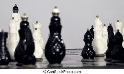 White and black chessfigures scattered around the board -...