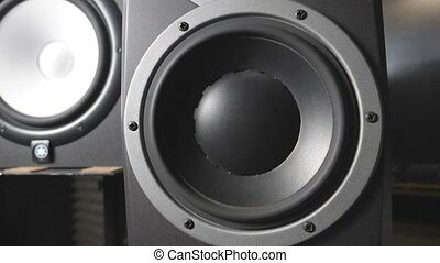White and black speaker pulsating and vibrating from sound on low frequency. Close up of moving sub-woofers on recording studio. Work of modern high fidelity loudspeaker membranes. Slow motion.